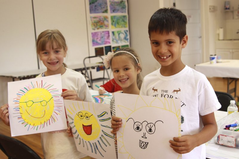 3 Summer Campers holding up their sun drawings