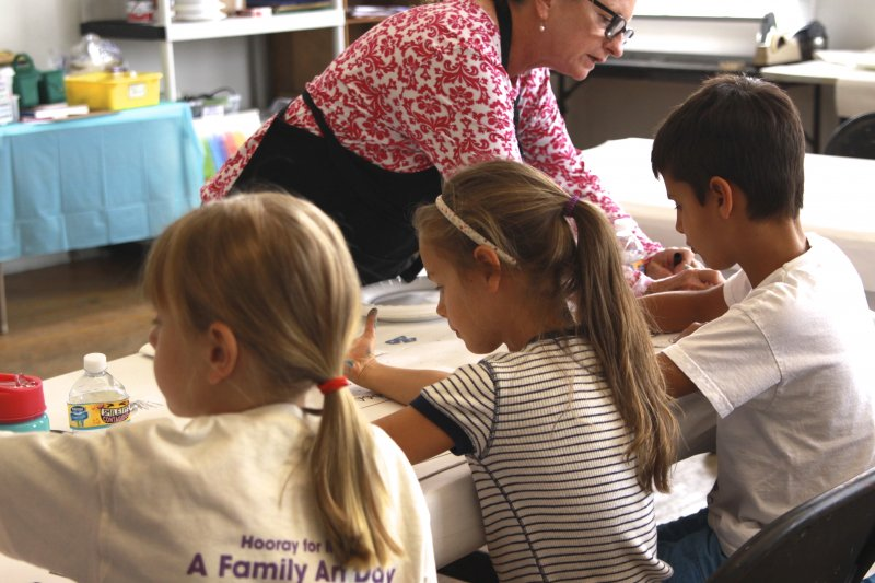 A Summer Camp teacher helping 3 campers with their drawings