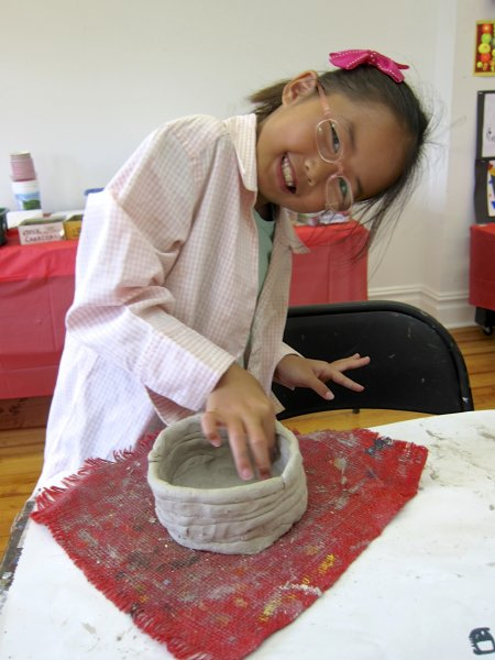 Summer camper building a clay pot by hand