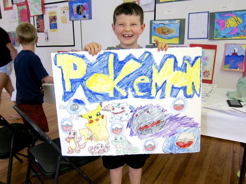 Summer camper showing off his cartoon drawing
