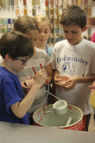 Summer campers glazing their clay pots