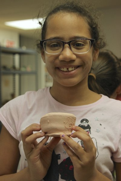 Summer camper showing off her clay pot