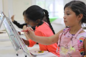 Children painting with easels in a Paint! class at The Center