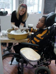 A student using The Center's wheelchair accessible pottery wheel with the help of his instructor.