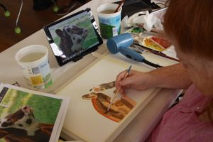Student at The Center painting a cow using watercolor paints.